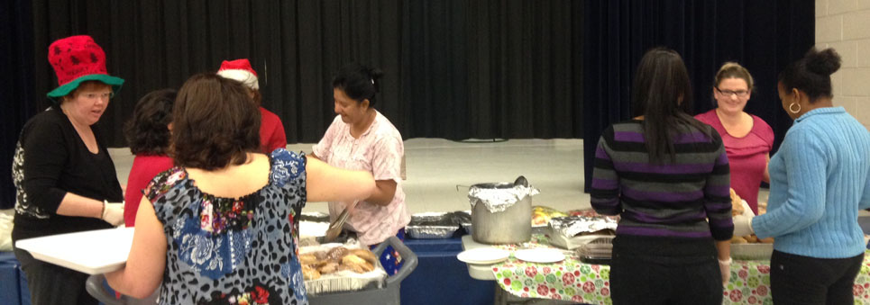 Parents wearing Christmas hats serving lunch to students