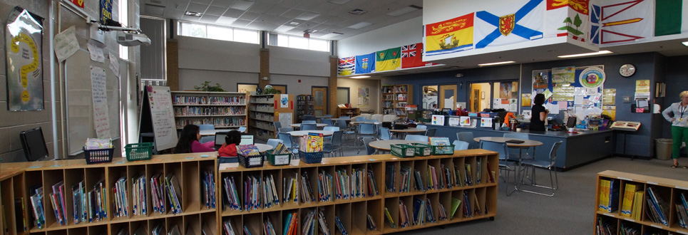 St. Teresa of Calcutta Catholic School library. Shelves of books, tables and chairs and posters and flags decorate the walls.