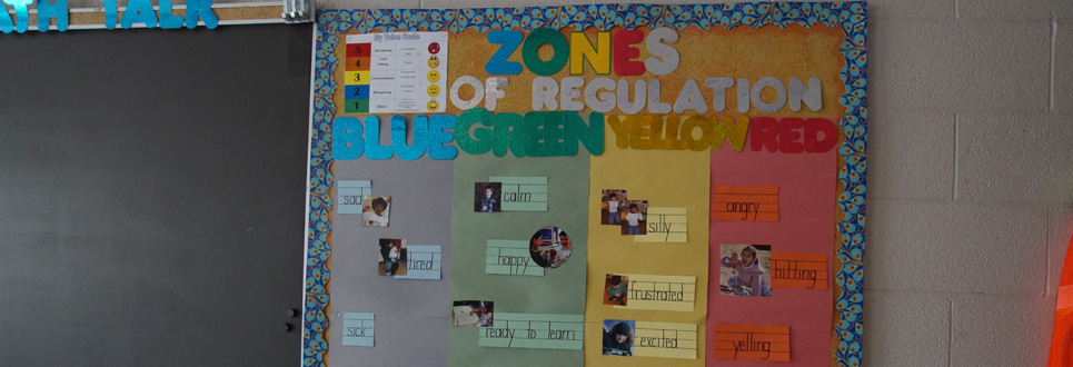"""Zones of Regulations"" bulletin board with ""Blue, Green, Yellow and Red"" sections with varying feelings under each one."